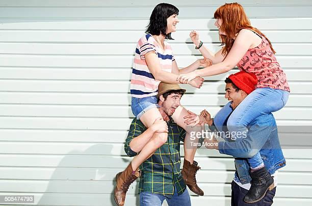 four friends having piggybacks play fighting