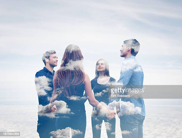 four friends holding hands with clouds. - cult stock pictures, royalty-free photos & images