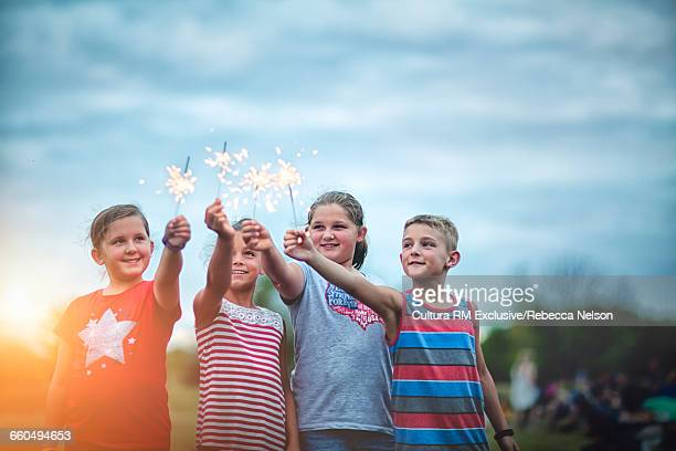 Four friends holding lit sparklers in air at Fourth of July celebration