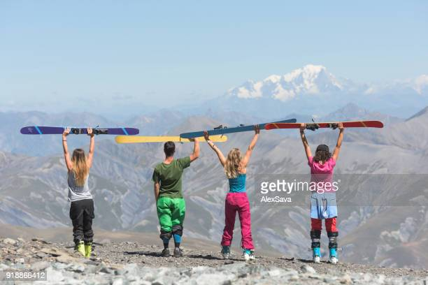 Four friends holding up their skis on top of the mountain