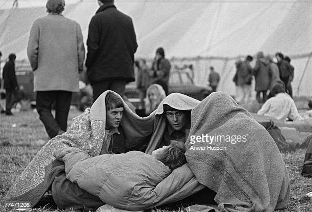 Four friends huddle under blankets at the Isle of Wight Festival in Wootton, 30th/31st August 1969.
