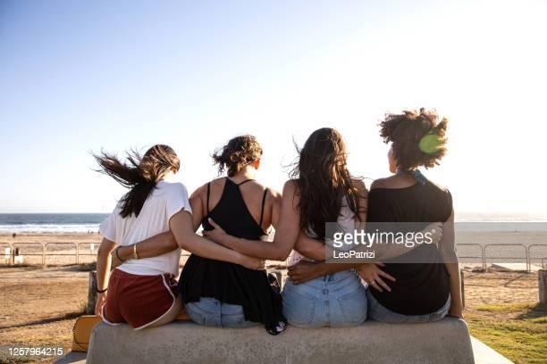 quattro amici che si abbracciano seduti in panchina di fronte a una spiaggia - four people foto e immagini stock