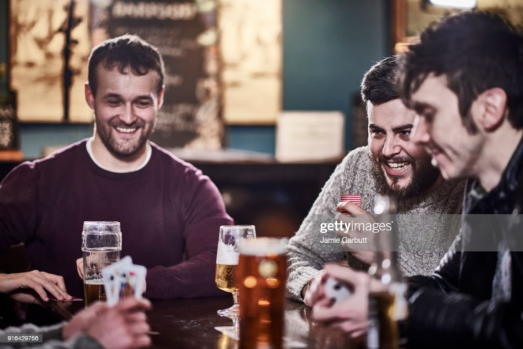 Four friends in a club drinking and playing cards : Foto de stock