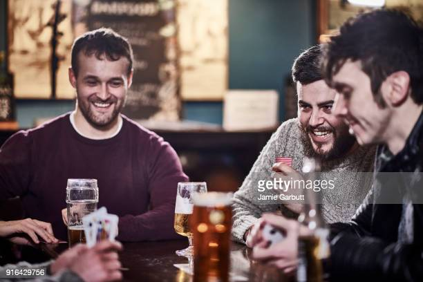 four friends in a club drinking and playing cards - ポーカー ストックフォトと画像