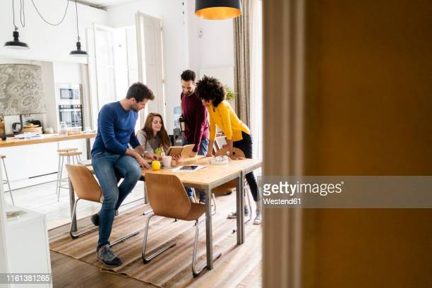 four friends in dining room at home with book - roommate stock pictures, royalty-free photos & images