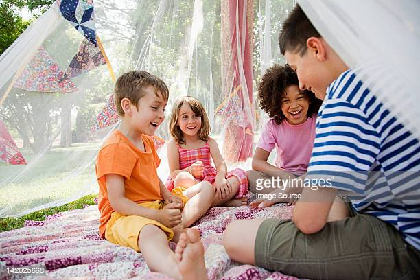 Four friends in summer netting tent