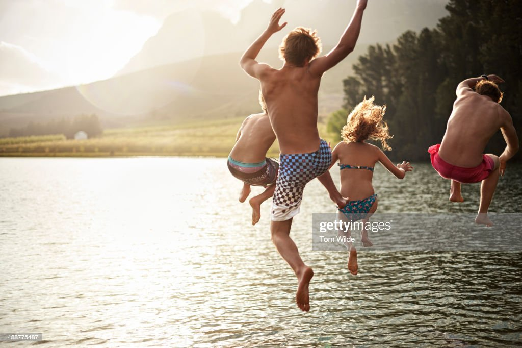 four friends jumping into a lake in the mountains : Stock Photo