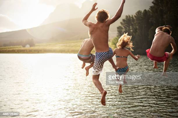four friends jumping into a lake in the mountains - lago imagens e fotografias de stock