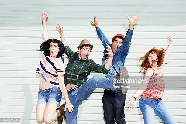 four friends jumping up in air