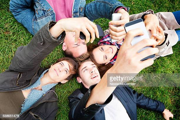Four friends laying on the ground shooting selfies