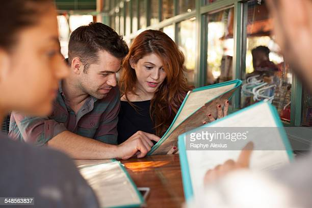 four friends looking at menus in vegetarian restaurant - menu stock pictures, royalty-free photos & images