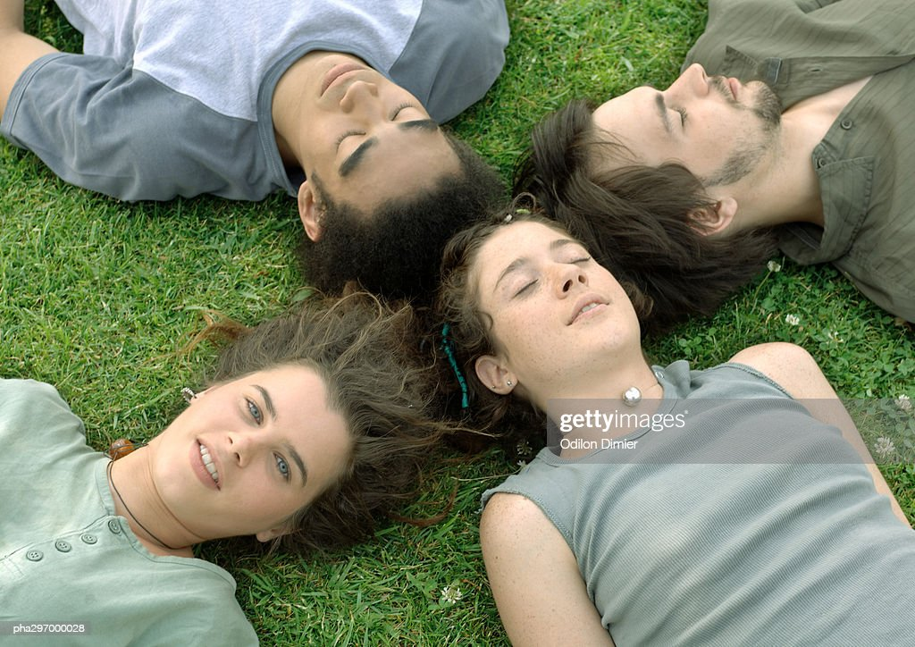Four friends lying on grass with heads together : Stockfoto