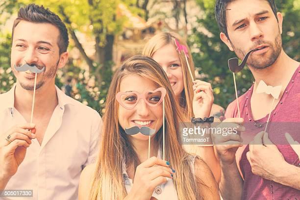 Cuatro amigos haciendo caras en una cabina de fotos postura