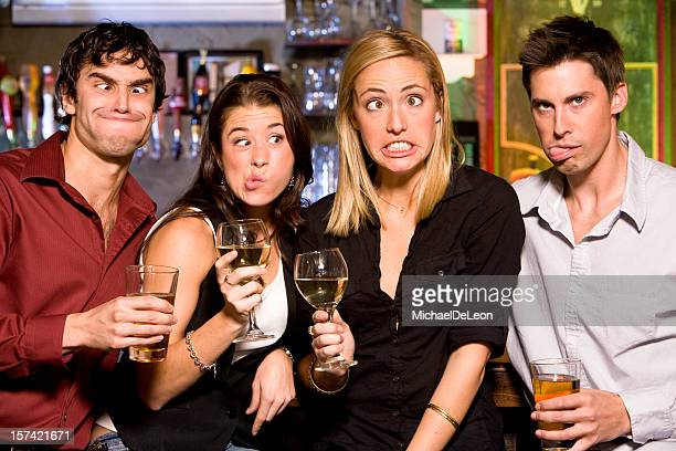 Four friends making funny faces at a bar with beer and wine