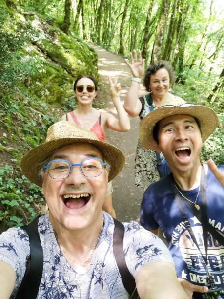 Four friends on a hike taking a selfie, Carennac, Quercy, Lot, Occitanie, France