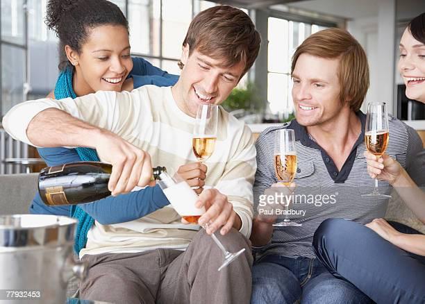 Quatre amis sur le canapé avec champagne