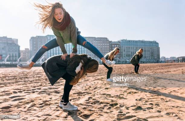 Four friends playing leapfrog on the beach