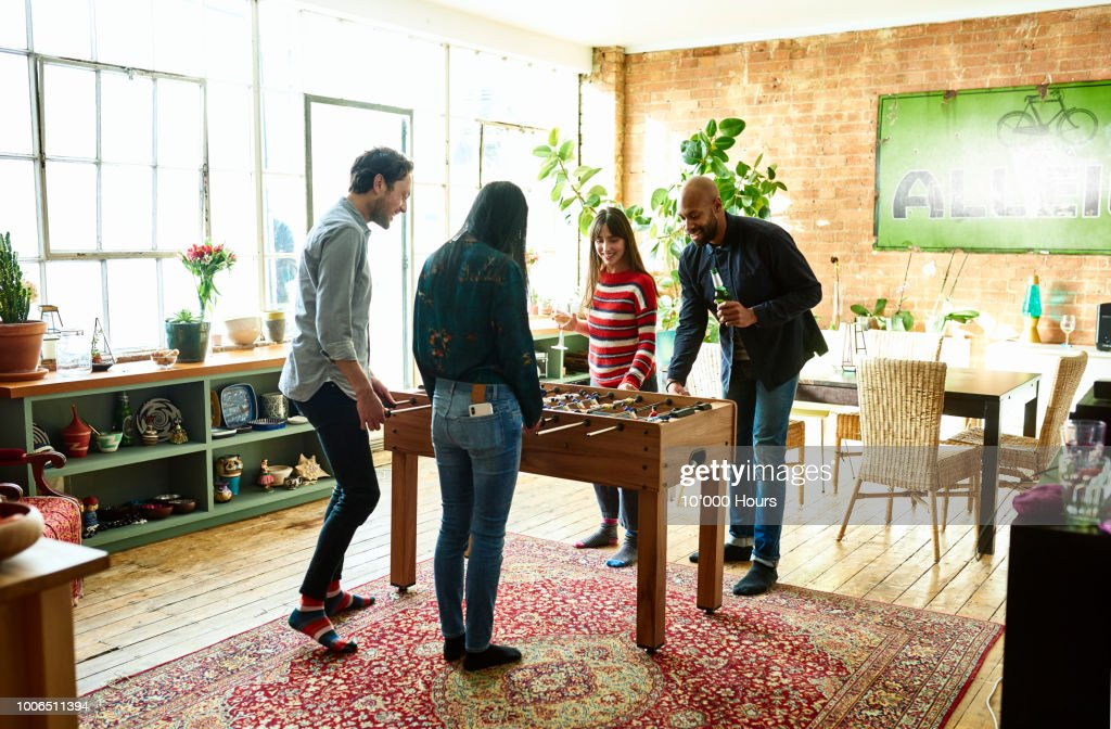 Four friends playing table football and drinking in modern hip apartment : Stock Photo