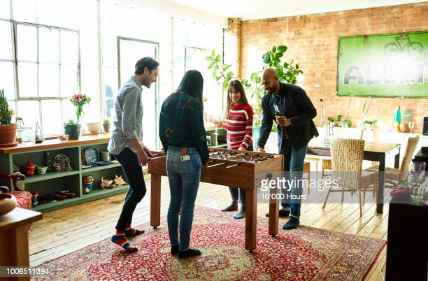 Four friends playing table football and drinking in modern hip apartment