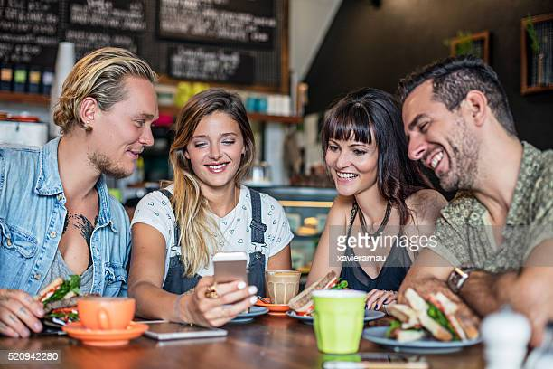 Four friends posting on social media in a coffee shop