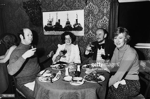 Four friends raise a glass during a meal at Sloop John B's at Chelsea Pier, 10th November 1974.