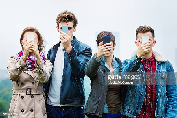 four friends shooting selfies on their mobile phones - enslaved stock pictures, royalty-free photos & images