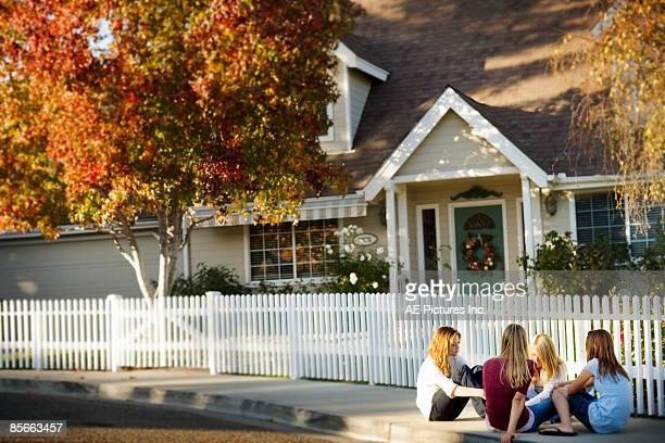 Four friends sit on suburban cul de sac