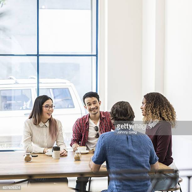 Four friends sitting at table in modern cafe