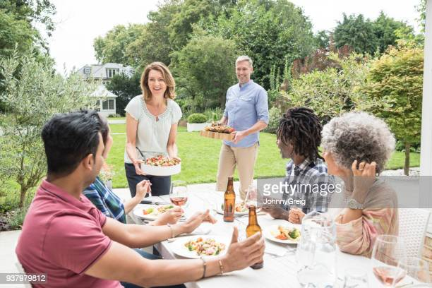 Four friends sitting at table with mature woman serving food