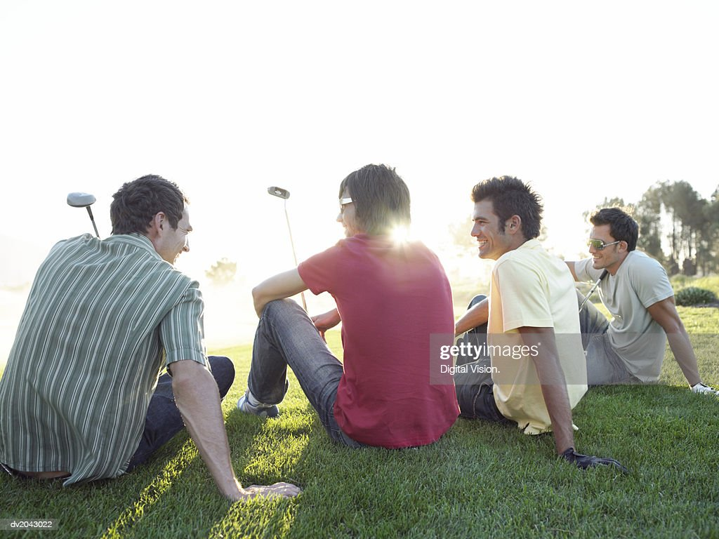 Four Friends Sitting in a Line on a Golf Course : Stock Photo