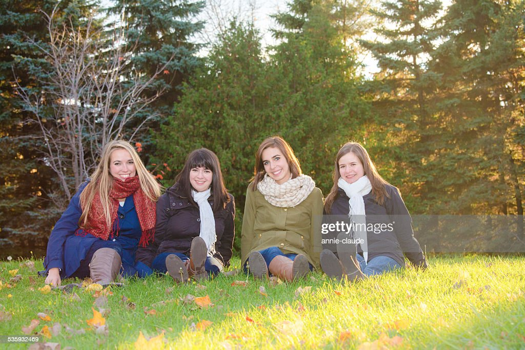 Four friends sitting in a park in fall : Stock Photo