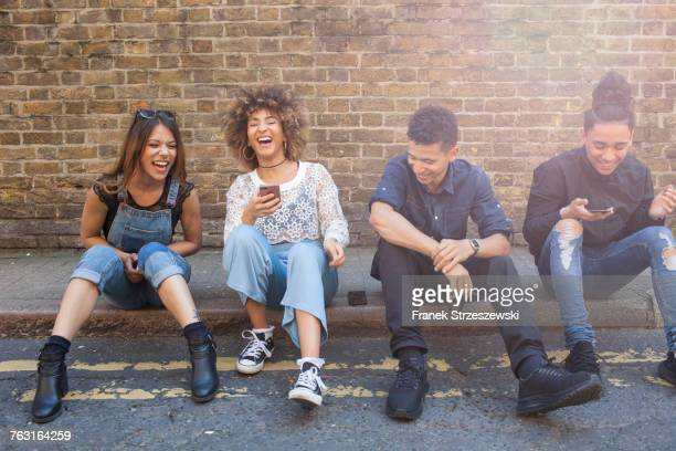 four friends sitting in street, laughing, young woman holding smartphone - curb stock pictures, royalty-free photos & images