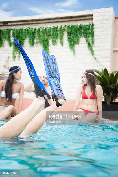 Four friends sitting in the pool, feet with flippers in the air