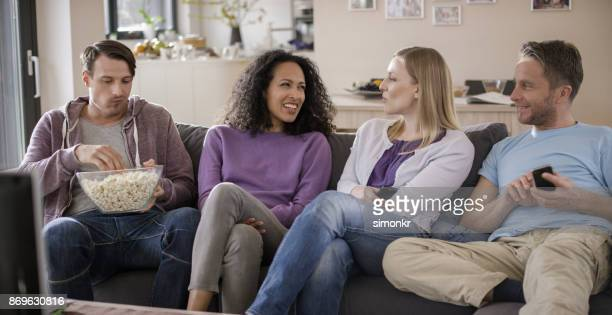 Four friends sitting on sofa in living room