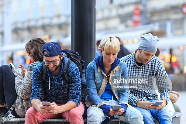 Four friends sitting on street and typing on smart phones