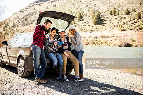 Four friends sitting on their tailgate.