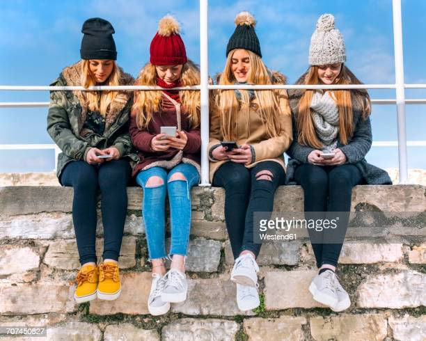 Four friends sitting side by side on a wall text messaging