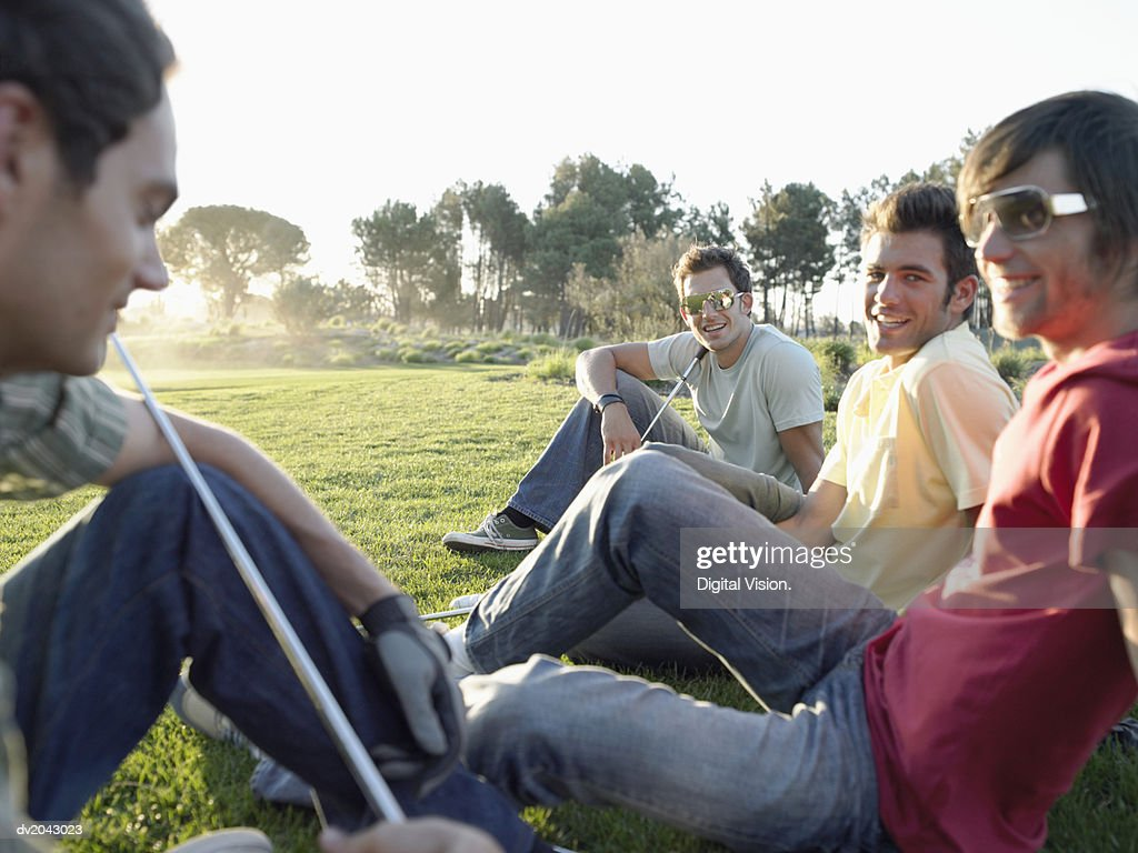 Four Friends Sitting Together on a Golf Course : Stock Photo