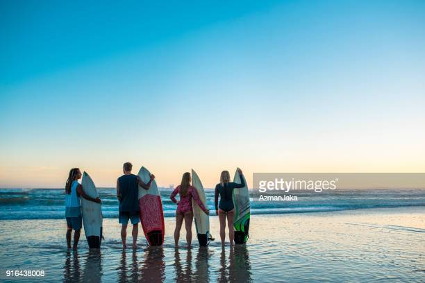 Four friends standing at the beach with surfboards