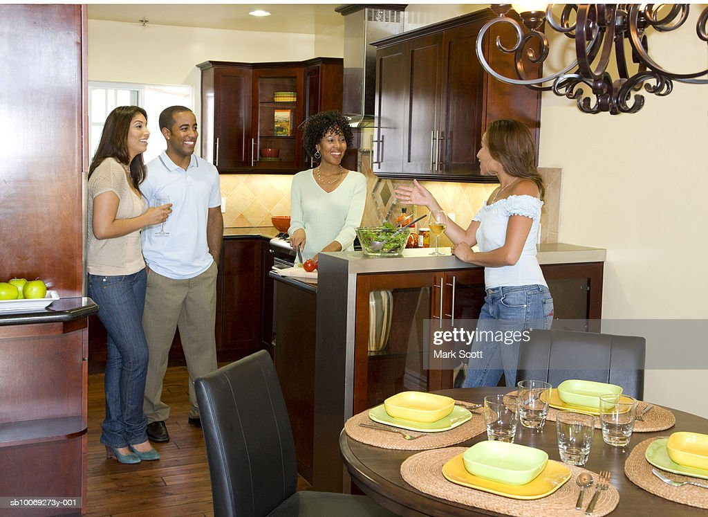 Four friends talking in kitchen : Stockfoto