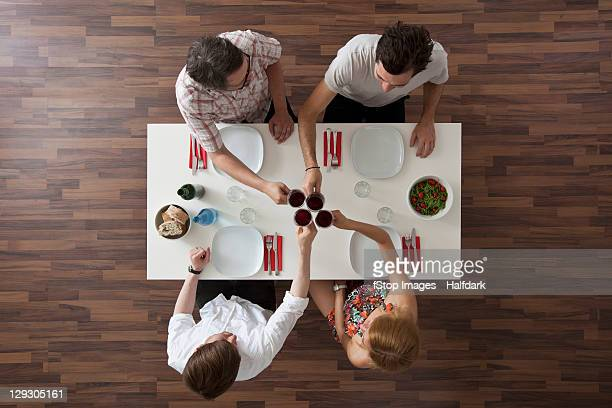 Four friends toasting at a dinner party, overhead view