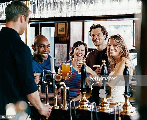 Four Friends Toasting Drinks in a Pub while a Barman Fills a Glass