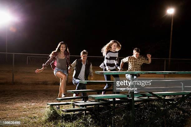 Four friends walking over bleachers at night