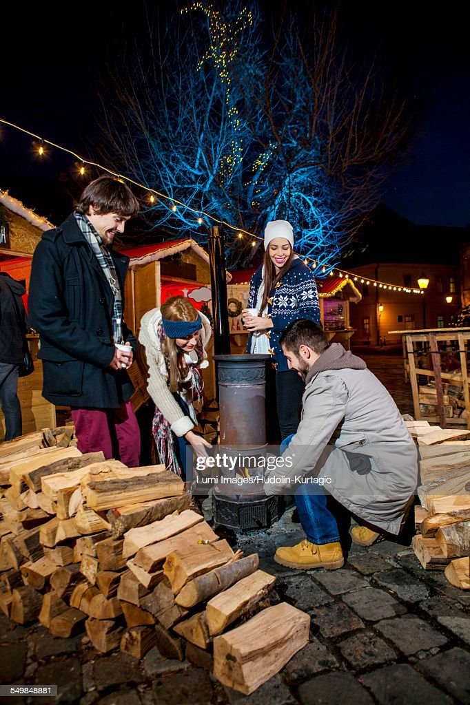 Four friends warming up by stove at Christmas Market : Stock Photo