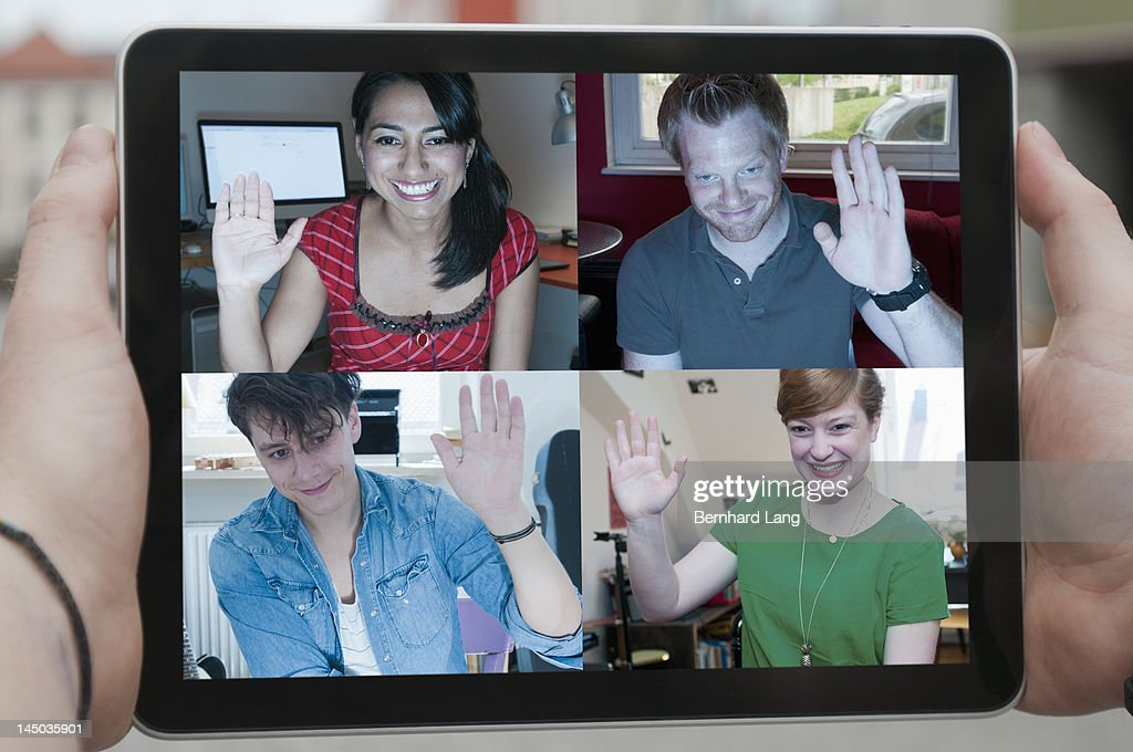 Four friends waving online, displayed on laptop : Stock Photo
