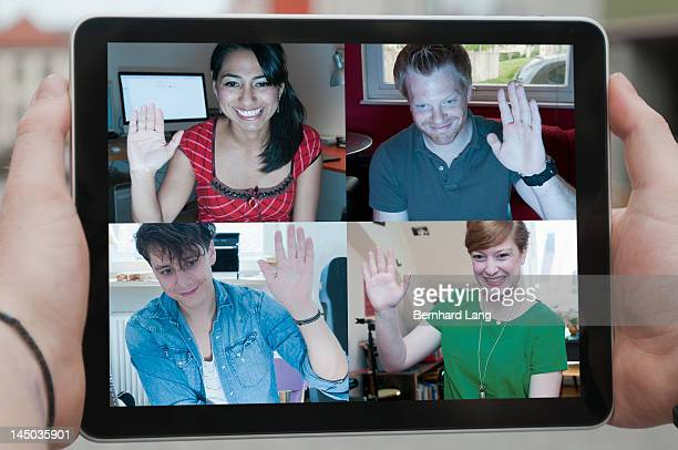 Four friends waving online, displayed on laptop