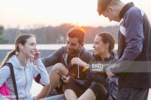 Four friends, wearing sports clothing, chatting, outdoors