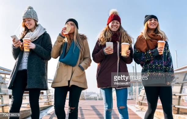 Four friends with coffee to go and cell phones walking on a bridge in winter