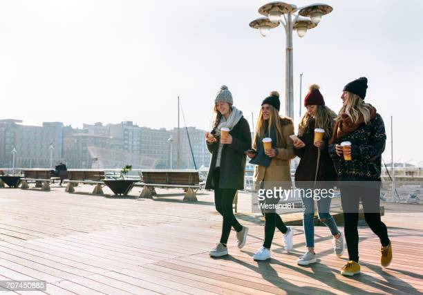 Four friends with coffee to go and cell phones walking on promenade in winter