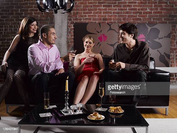 Four friends with drinks at party